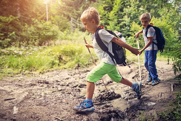 Little campers hiking on muddy path at kids summer camps