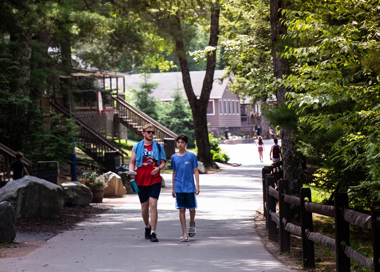 Counselor and Camper Walking Together at Summer Camp