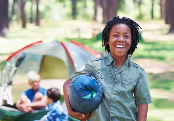 Smiling Kid Camping out at Kids Summer Camp