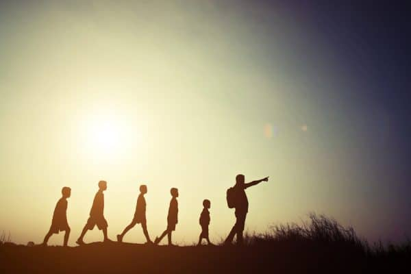 Silhouettes children and parent walking with backpacks. Time to go travel together.